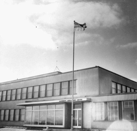 Drapeau régional hissé le 11 juin 1955 sur le mat du Laboratoire d'Arvida et du bureau principal de l'Alcan d'Arvida. Source: Société historique du Saguenay-P002, S7, P07418-01