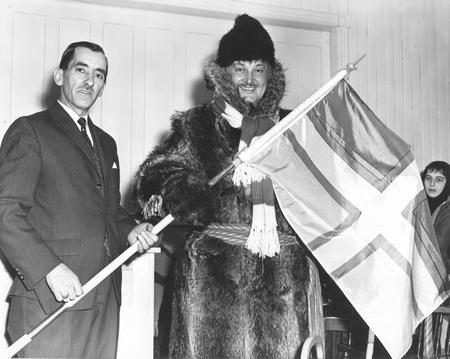 Un drapeau régional offert au chanteur Jacques Labrecque, le 13 février 1963 à Métabetchouan. Source: Société historique du Saguenay-FPH-65, P01106