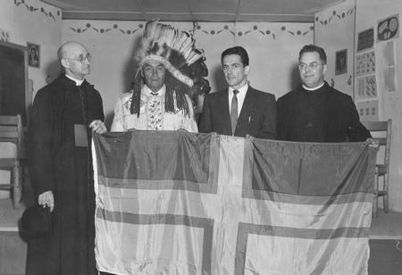 Présentation d'un drapeau régional au chef de la Réserve autochtone de Mashteuiatsh, le 9 juin 1956 dans le cadre du centenaire de «Pointe-Bleue». De gauche à droite: Chanoine Victor Tremblay, Gabriel Kurtness, chef de Mashteuiatsh, Louis-Marie Tremblay du «Réveil», R.P. Aram Éthier, curé de Pointe-Bleue. Source: Société historique du Saguenay-P002, S7, P07857-01