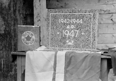 Bénédiction de la pierre angulaire, de l'édifice de la Compagnie de téléphone Saguenay-Québec à Chicoutimi. On aperçoit à gauche l'étui de plomb contenant les documents à déposer dans la pierre, et sous la pierre, le drapeau régional. Société historique du Saguenay-P002, S7, P01120-01